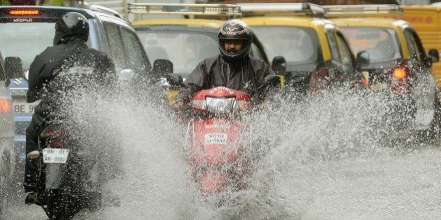 An Indian motorcyclist rides along a flooded street after heavy rain in Mumbai on July 16, 2014. The...