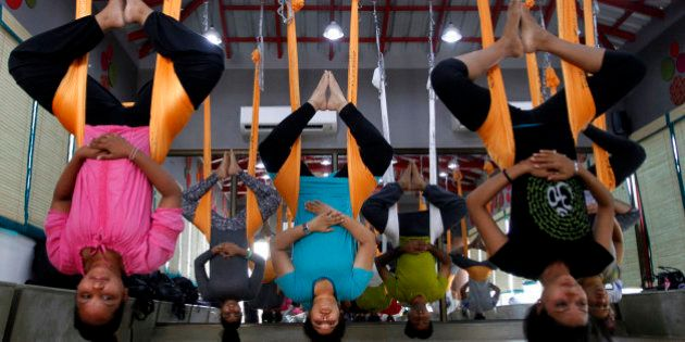 In this Thursday, June 18, 2015, photo, Indians perform anti gravity aerial yoga in Ahmadabad, India....