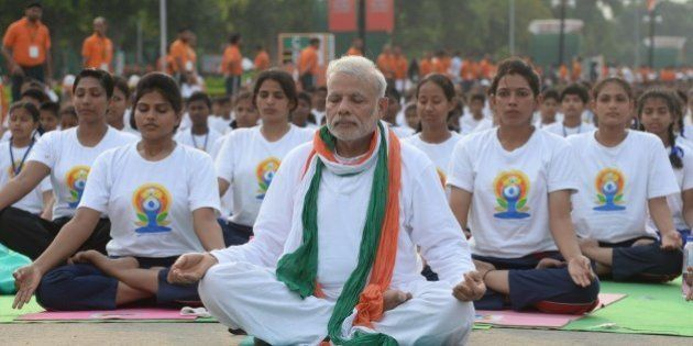 Indian Prime Minister Narendra Modi (C) participates in a mass yoga session along with other Indian yoga...