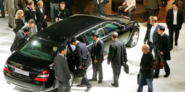 Visitors take a look at the armored Mercedes Pullman Guard at the first press day of the Paris Auto Show,...