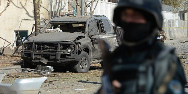An Afghan policeman stands guard at the site where a suicide bomber targeted a vehicle convoy of Afghan...