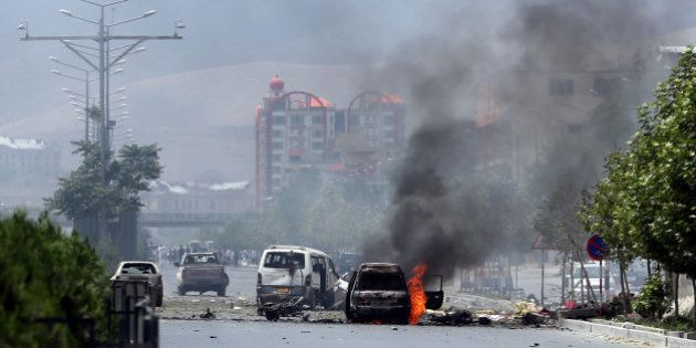 Fire and smokes rise at the site of a suicide attack during clashes with Taliban fighters in front of...