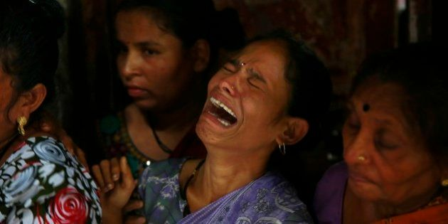 A relative of Lata Jadhav, one among the dozens who died after drinking tainted liquor, cries during...