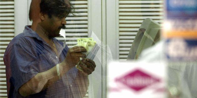 NEW DELHI, INDIA: An Indian man withdraws money at a IDBI's ATM counter in New Delhi, 11 May 2004. Indian...
