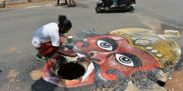 Indian artist Badal Nanjundaswamy uses the opening of an unattended manhole in the middle of a road as...