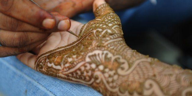 An Indian Muslim woman gets her hands decorated with traditional henna designs at a roadside stall ahead...