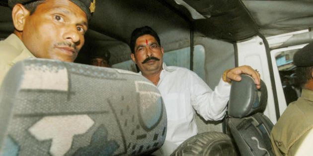 Member of Bihar's ruling Janata Dal (People's Party), Anant Singh (R) waits in the police van on his...