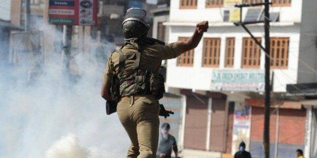 An Indian security personnel throws a rock towards Kashmiri protestors during clashes in Srinagar on...
