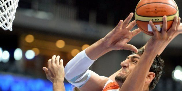 Satnam Singh Bharama (R) of India takes a shot against Kazakhstan during the Asian basketball championship...