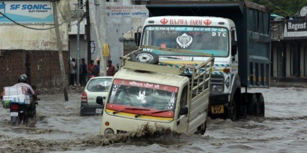 Indian commuters make their way along a water-logged road after a monsoon rainshower in Jalandhar on...