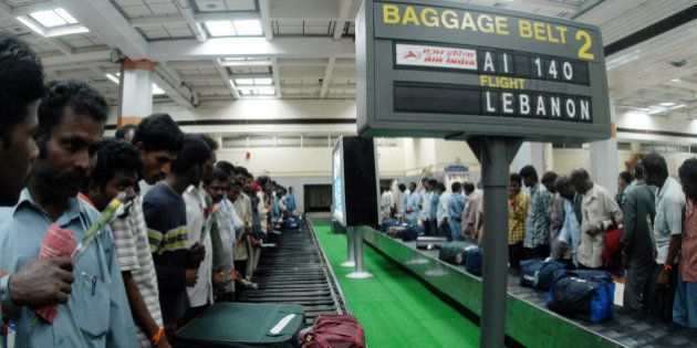 Indians from Lebanon wait for their baggage near a conveyor belt inside Madras international airport...
