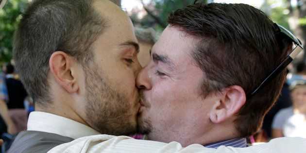 Ryan Jones, left, and Ruben Vallejo kiss after getting married during a rally in response to the Supreme...