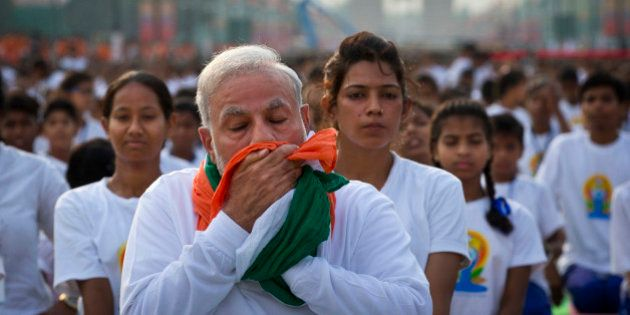 Indian Prime Minister Narendra Modi wipes his sweat with a scarf made in the colors of Indian tricolor...