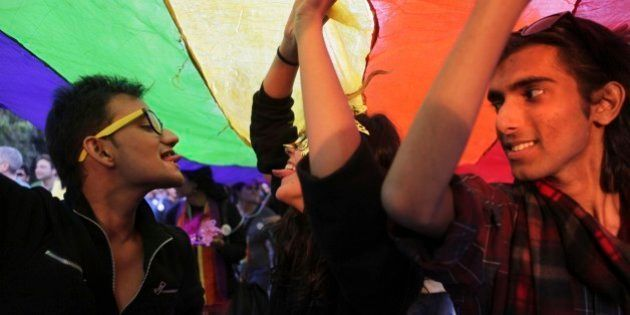 Gay rights activists display a rainbow-colored banner as they march in New Delhi, India, Sunday, Nov....
