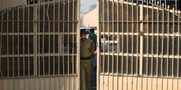An Indian police officer prepares to close one of the gates at Tihar Jail, the largest complex of prisons...