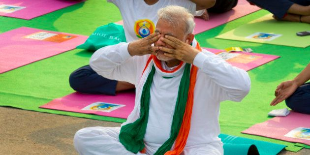Indian Prime Minister Narendra Modi, performs breathing exercise during yoga along with thousands of...