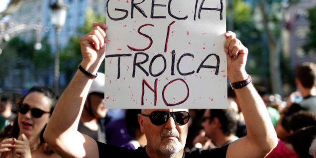 A man holds a banner during a pro Greece demonstration at the European Union Office in Barcelona, Spain,...