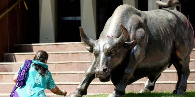 A sub-broker makes flower offerings before the statue of a bull outside the Bombay Stock Exchange (BSE)...