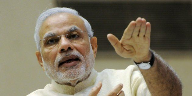 Indian Prime Minister Narendra Modi gestures as he addresses a ceremony at the launch of 'Smart Cities...