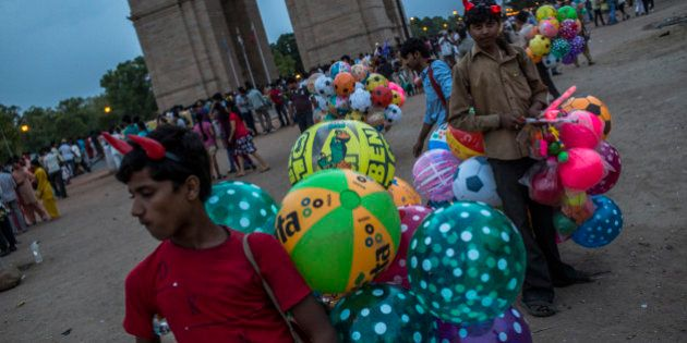 NEW DELHI, INDIA - JUNE 02: Boys selling balloons wait for customers at the India Gate monument on June...