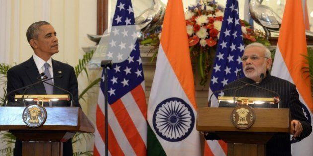 US President Barack Obama (L) watches as Indian Prime Minister Narendra Modi speaks during a joint press...