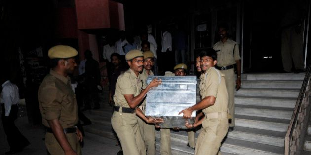 Policemen carry a trunk box containing legal documents relating to the Satyam Computer Services Ltd....