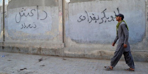 A Pakistani man walks past a wall graffiti reading 'Abu Bakr al-Baghdadi', leader of the Islamic State...