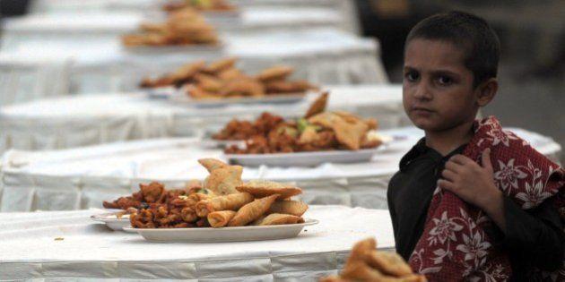 A Pakistani boy stands beside Iftar food to break their Ramadan fast on a street in Karachi on July 3,...
