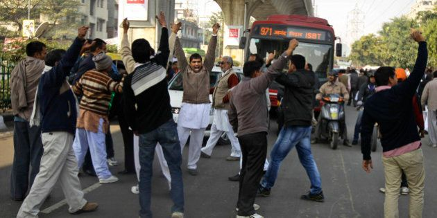 Supporters of former Haryana state Chief Minister Om Prakash Chautala stop traffic and shout slogans...