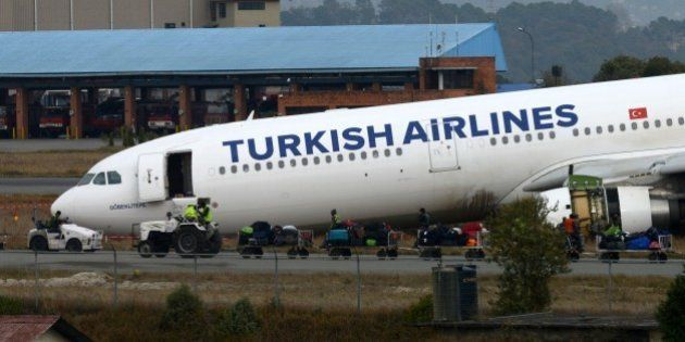 Airline workers move passenger luggage from a Turkish Airlines plane after it slid off the tarmac at...