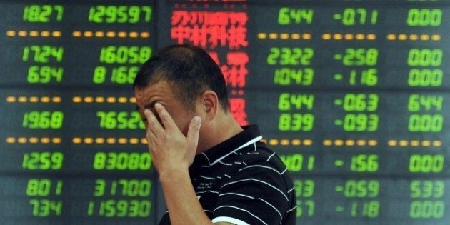 An investor reacts in front of a screen showing stock market movements in Fuyang, eastern China's Anhui...