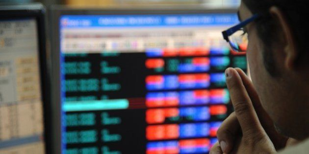 An Indian stock trader monitors share prices during intra-day trade at a brokerage house in Mumbai on...