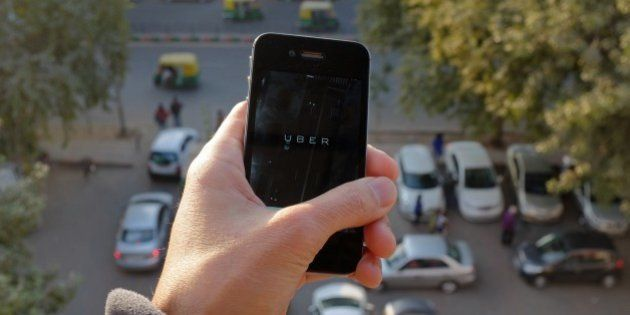 The Uber smartphone app, used to book taxis using its service, is pictured over a parking lot as auto-rickshaws...