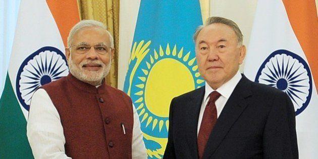 Kazakh President Nursultan Nazarbayev (R) shakes hands with Indian Prime Minister Narendra Modi during...