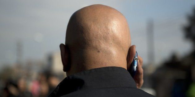 A police officer speaks by mobile outside the cemetery where 'Don Diego', father of Argentina's former...