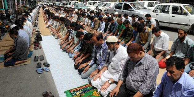 Kashmiri Muslims perform congregational prayers on a street during the first day of the fasting month...