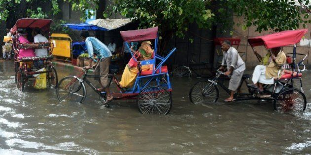 Indian cycle rickshaw drivers ferry commuters through floodwaters on a street of New Delhi on July 9,...
