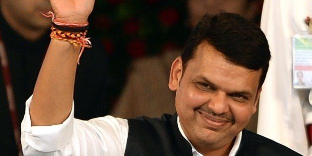 India's Maharashtra state new Chief Minister and BJP leader Devendra Fadnavis waves towards crowd after...