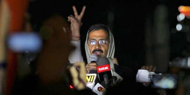 A supporter flashes a victory sign as New Delhi Chief Minister Arvind Kejriwal, center, announces calling...