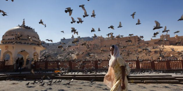 [UNVERIFIED CONTENT] A woman is walking by the Amber Fort, surrounded by pigeons flying all over the...