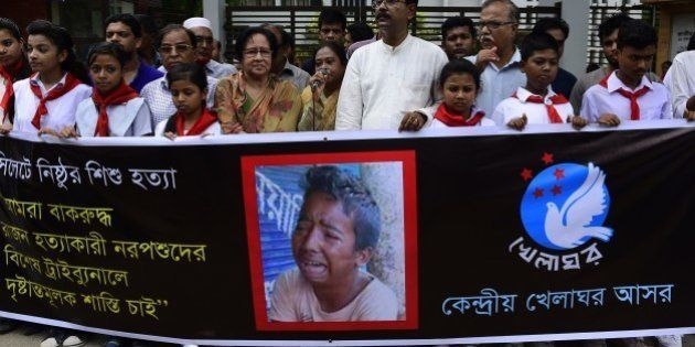 Bangladeshi protesters carry a banner during a demonstration against the lynching of a 13-year-old boy...