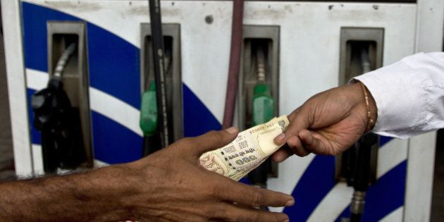 An Indian comsumer (R) pays a petrol-pump attendant in New Delhi on July 30, 2013. India's central bank...