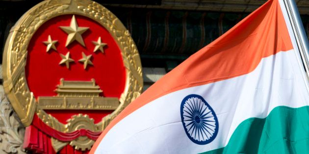An Indian national flag is flown next to the Chinese national emblem during a welcome ceremony for visiting...