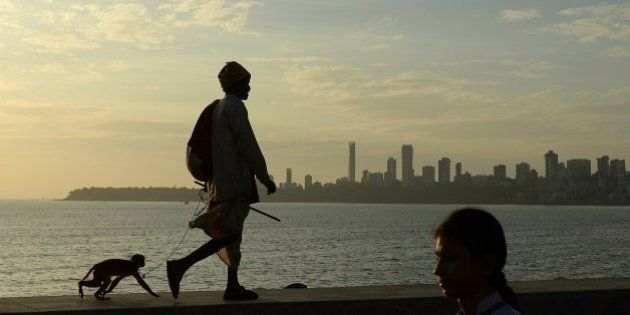 An Indian man leads his pet monkey on a leash along the seafront in Mumbai on January 21, 2015. India...