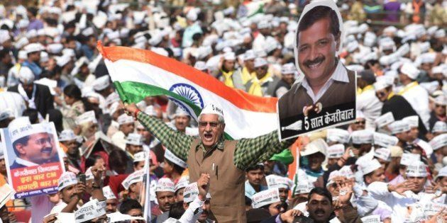 Supporters of the Aam Aadmi Party (AAP) shout slogans as they watch leader Arvind Kejriwal being sworn...