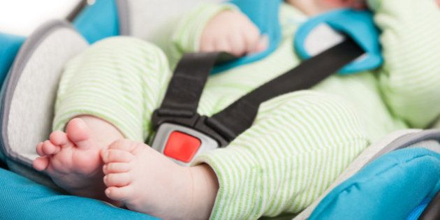 Little smiling baby child fastened with security belt in safety car