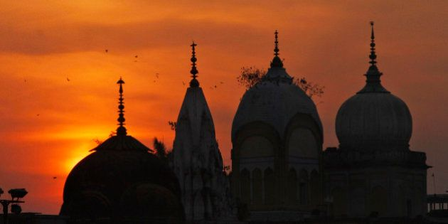 Birds fly at sunset over a Hindu temple on the 20th anniversary of the Babri mosque demolition in Ayodhya,...