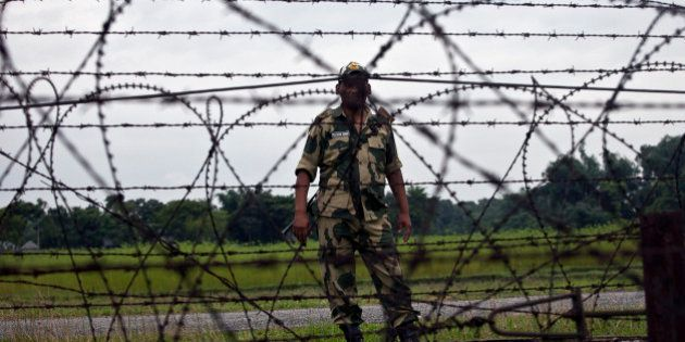 LALMONIRHAT DISTRICT, BANGLADESH - JULY 10: A member of the Indian BSF stands across from the India/Bangladesh...