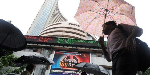 Indian residents walk past the Bombay Stock Exchange (BSE) during intra-day trading at a brokerage house...