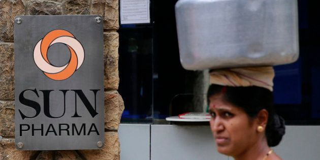 An Indian woman carries a water vessel as she walks past the office of Sun Pharmaceutical in Mumbai,...